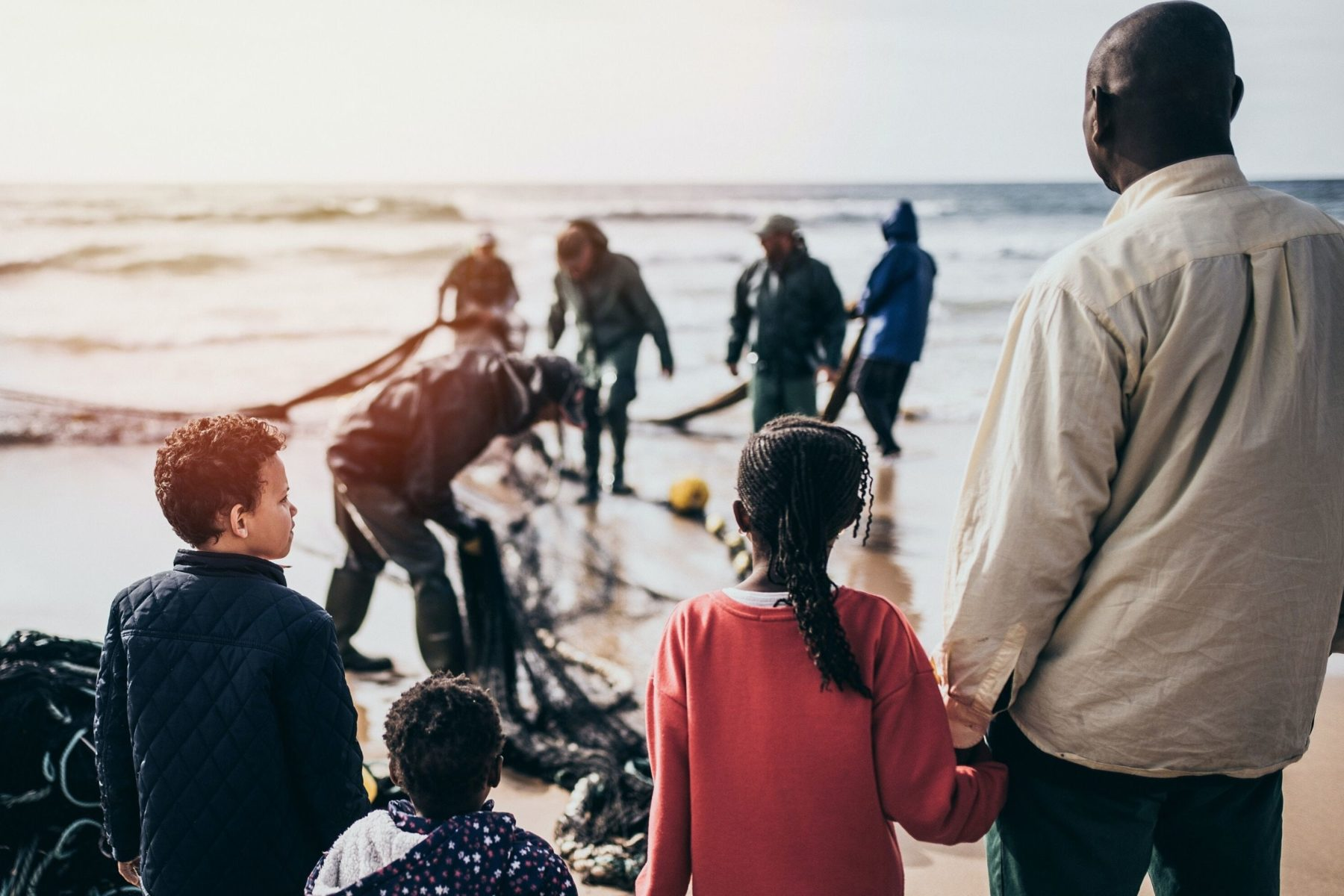 Refugees on a shoreline. One man and three children
