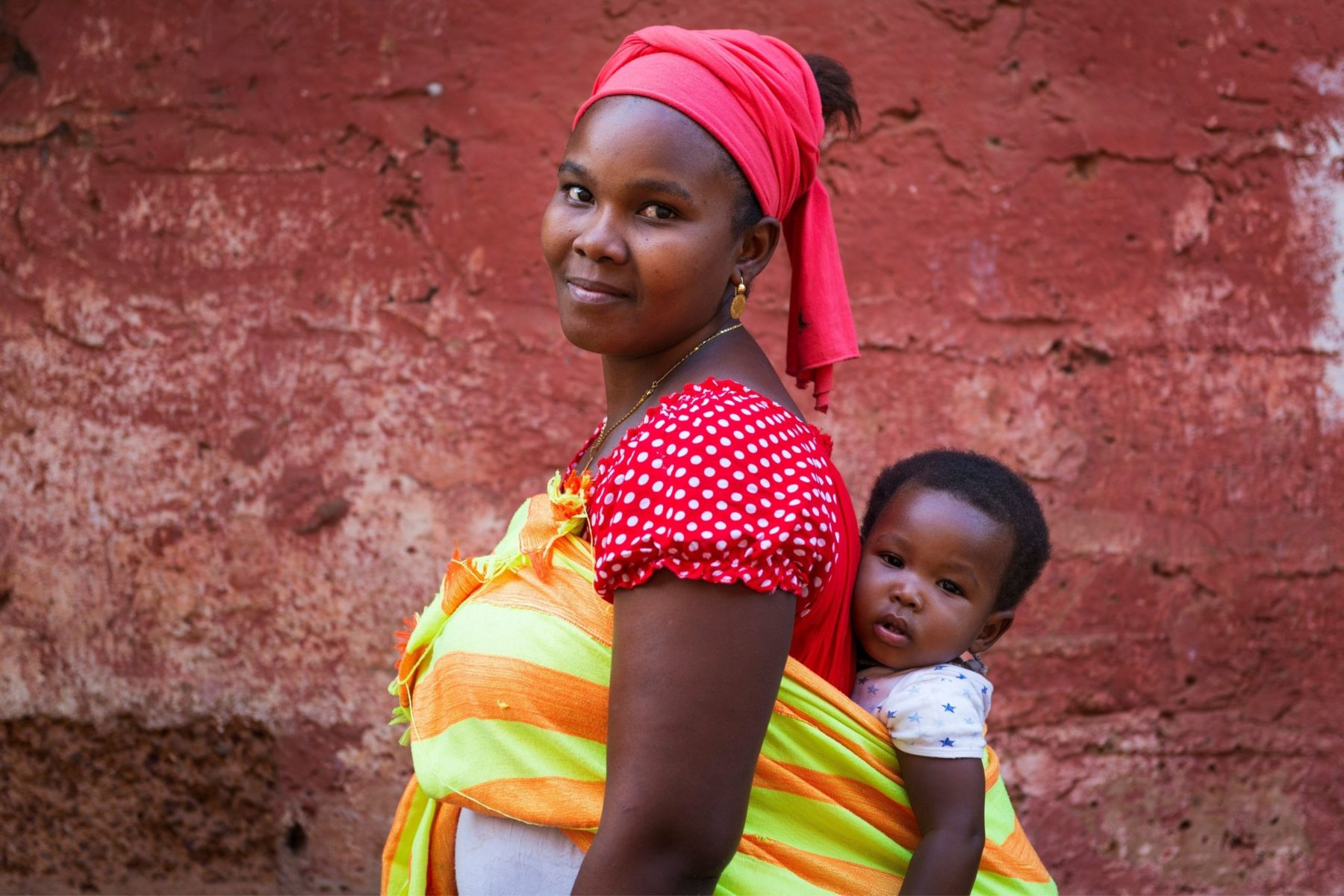 African woman carrying baby on her back